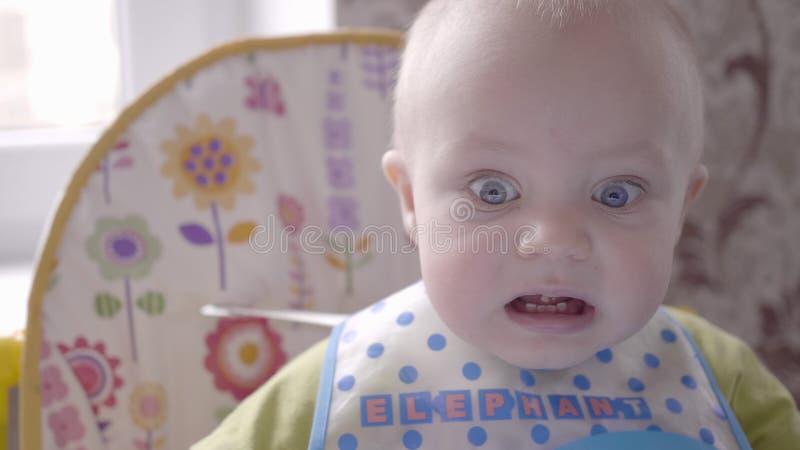 Il neonato bello alla tavola prende un biscotto in sua mano, mangiandola, guardando nella macchina fotografica e balbettando vici fotografie stock