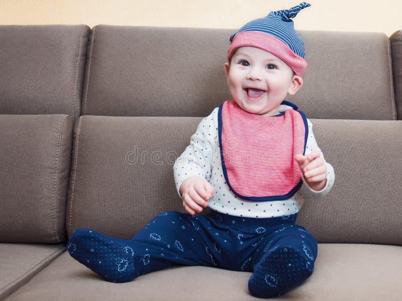 Il neonato caucasico weared la busbana francese che si siede sul sofà a casa fotografia stock libera da diritti