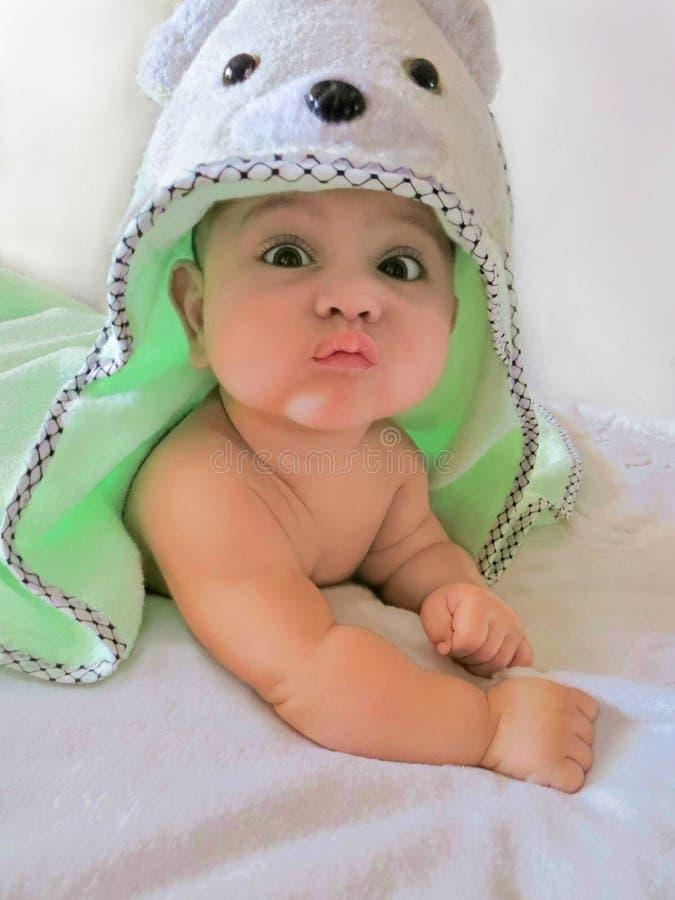 Il neonato con l'stagno-asciugamano d'uso sorpreso divertente della orso-testa del fronte è su un fondo bianco fotografie stock