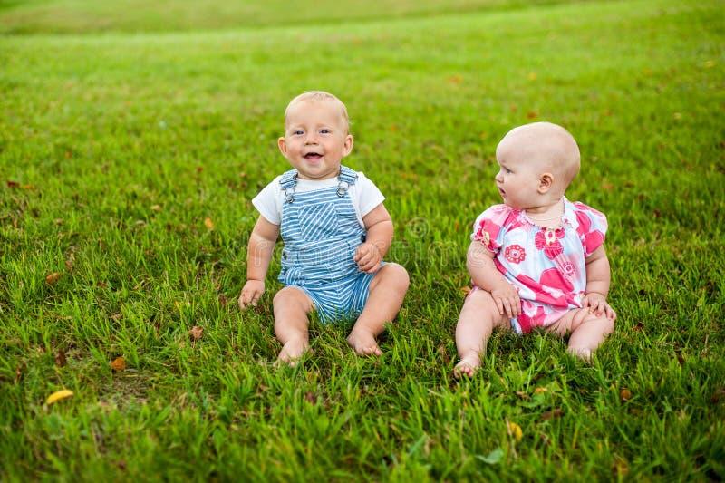 Il neonato felice due e un'età della ragazza 9 mesi, sedendosi sull'erba ed interagiscono, se parlano, esaminano fotografia stock libera da diritti