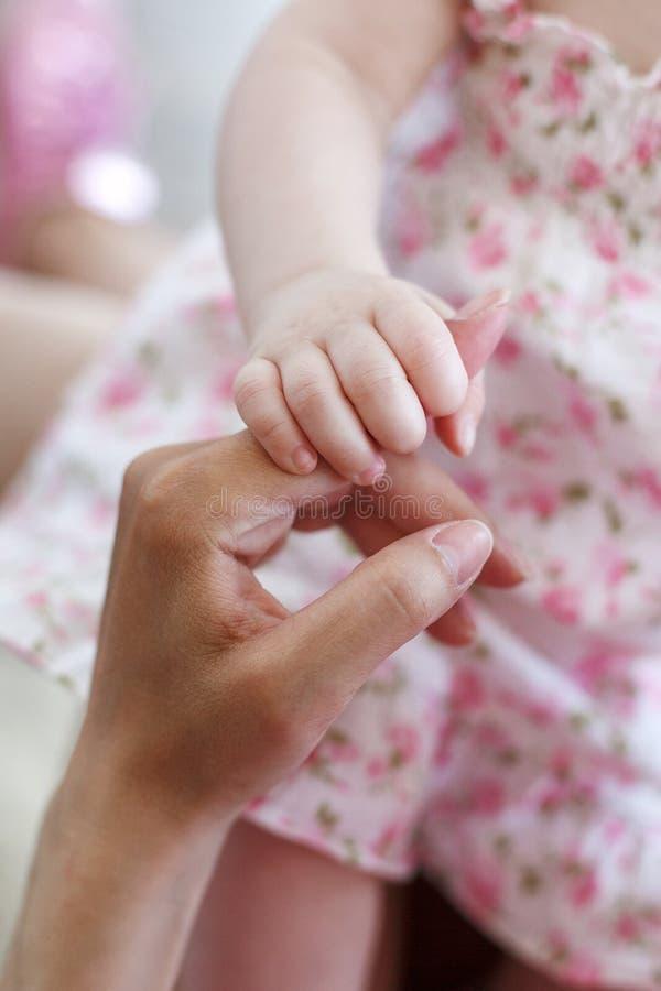 Il neonato, ha piegato la piccola maniglia rosa in un gomito e forte tiene un indice della mano di una madre fotografia stock libera da diritti