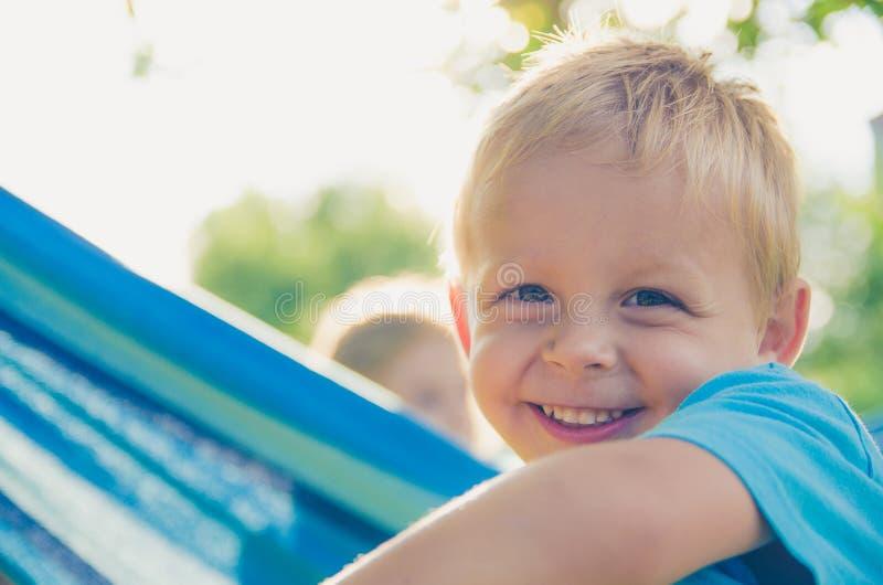 Il neonato ride un giorno soleggiato C'è un altro bambino sull'amaca nella parte posteriore del giardino immagine stock