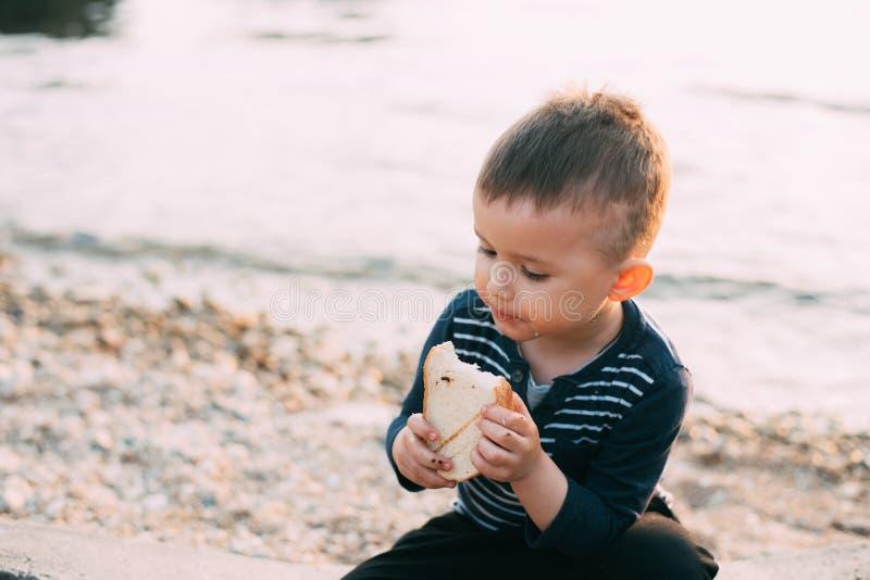 Il neonato sui precedenti del mare al tramonto che mangia un pezzo di pane ha tostato fotografia stock libera da diritti