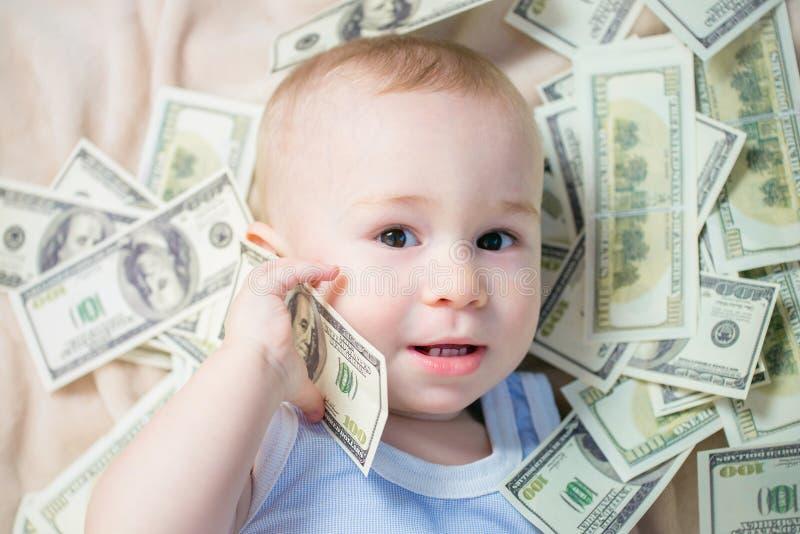Il neonato sveglio che gioca con molti soldi gradisce parlare sul telefono, americano cento dollari di contanti immagini stock
