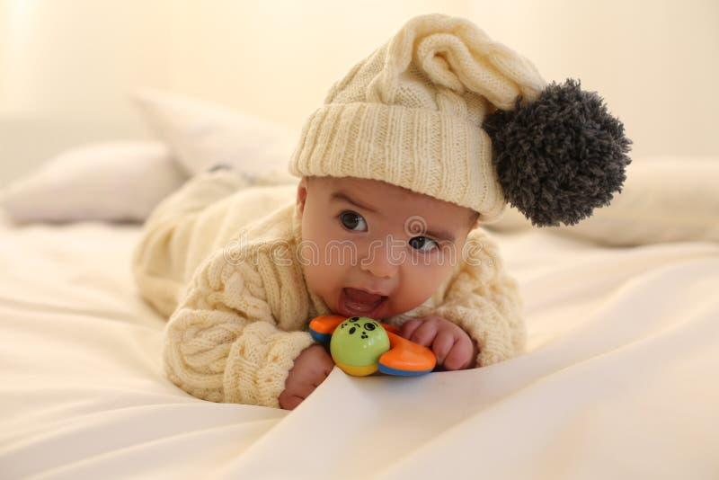 Il neonato sveglio, indossa i vestiti tricottati, divertendosi a casa accogliente immagine stock
