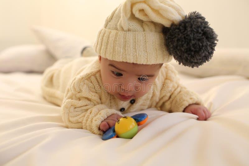 Il neonato sveglio, indossa i vestiti tricottati, giocanti con il giocattolo a casa accogliente fotografie stock libere da diritti