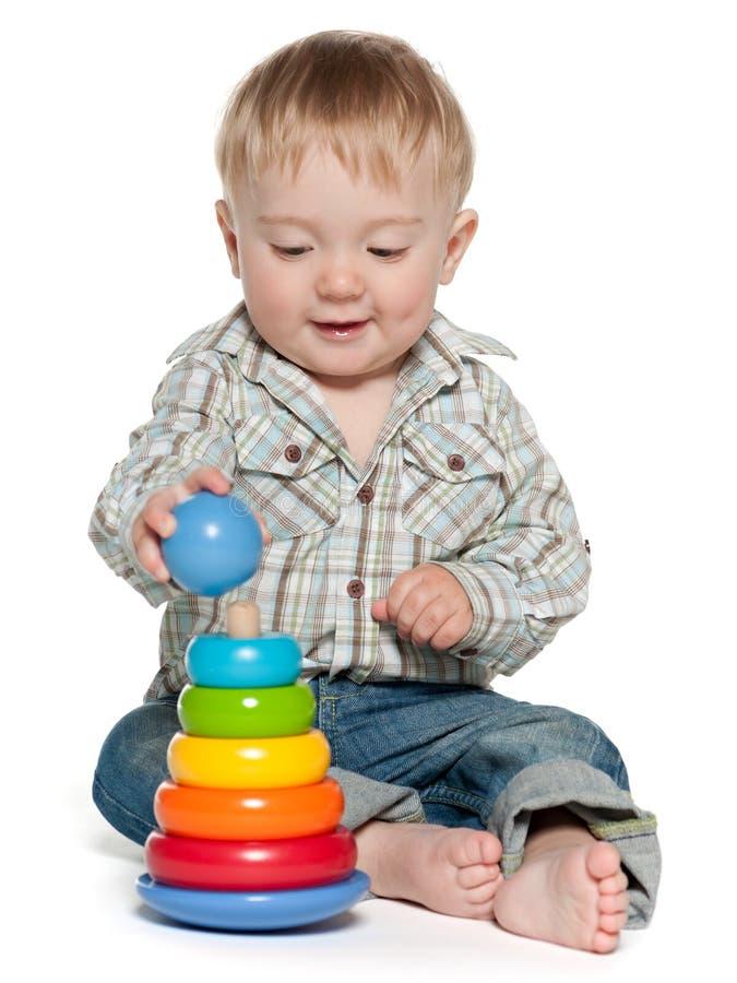Il neonato sveglio sta giocando con i giocattoli fotografie stock