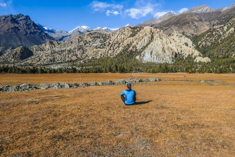 Il Nepal - uomo che si siede sul prato in Himalaya immagine stock libera da diritti