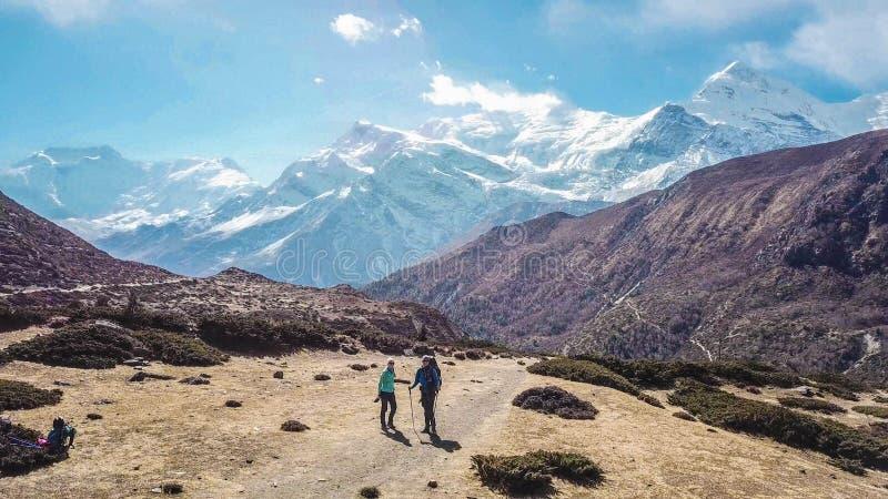 Il Nepal - viandanti davanti alle montagne innevate immagini stock libere da diritti