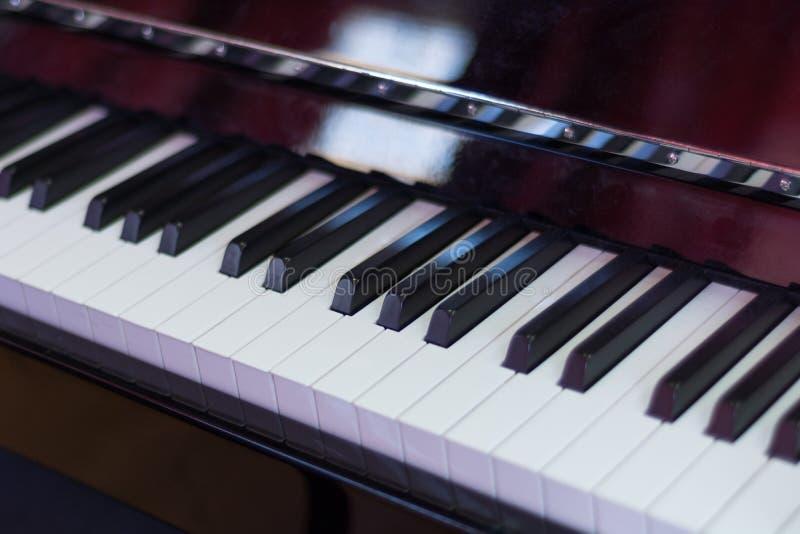 Il nero classico della tastiera di piano e con e scatola di legno marrone, chiavi musicali e strumento fotografia stock