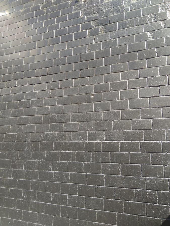 Il nero del muro di mattoni, illuminato da luce solare fotografia stock