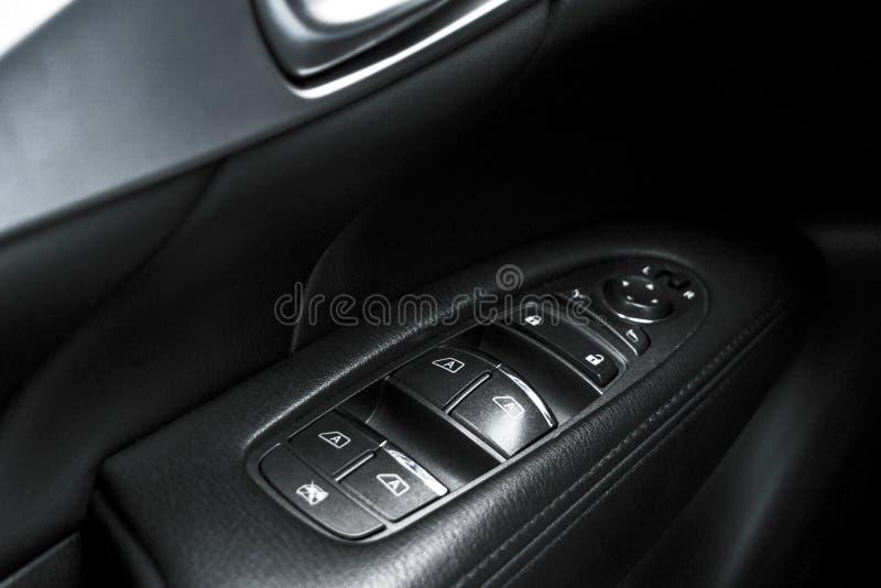 Il nero dell'automobile ha perforato i dettagli interni di cuoio della maniglia di porta con i comandi e gli adeguamenti delle fi fotografia stock libera da diritti