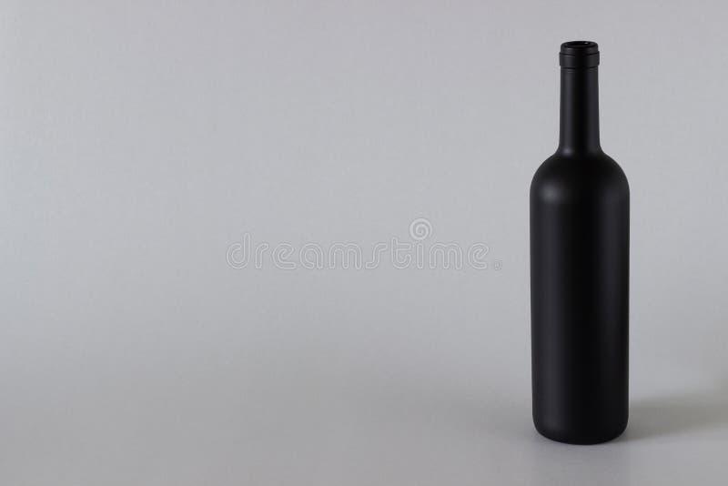 Il nero della bottiglia di vino su un fondo bianco immagine stock