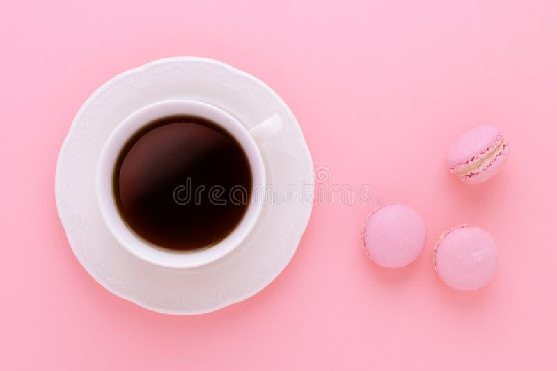 Il nero della tazza di caffè con i maccheroni fatti a mano su fondo rosa da sopra fotografia stock