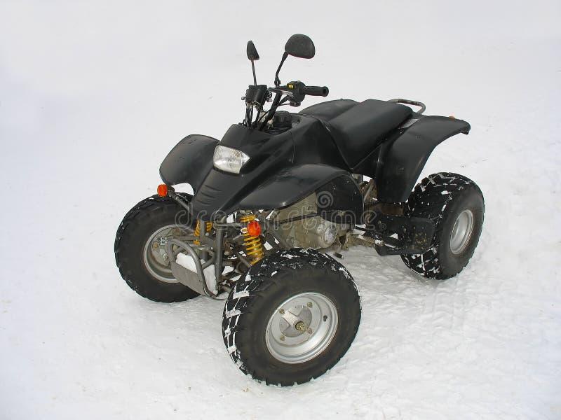 Il nero di ATV tutto il veicolo del terreno su neve bianca fotografie stock