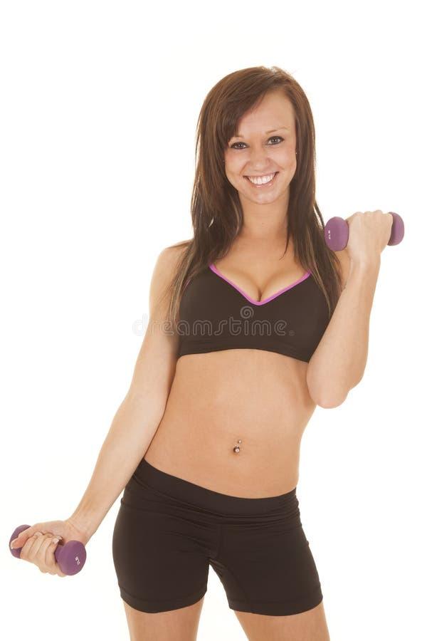 Il nero di forma fisica della donna mette i pesi in cortocircuito uno di porpora del reggiseno su fotografie stock libere da diritti