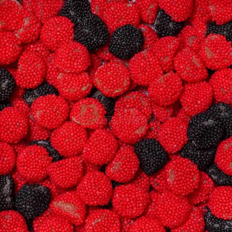 Il nero e caramelle del mirtillo rosso sotto forma di lamponi e di more immagini stock