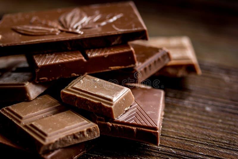 Il nero e fondo di legno della tavola dei pezzi del cioccolato al latte fotografia stock libera da diritti