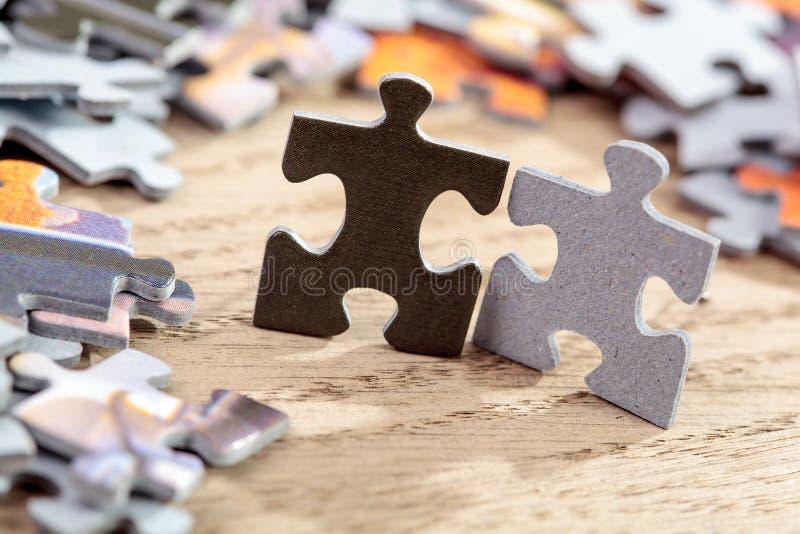 Il nero e Grey Jigsaw Puzzle Pieces sulla Tabella fotografia stock libera da diritti