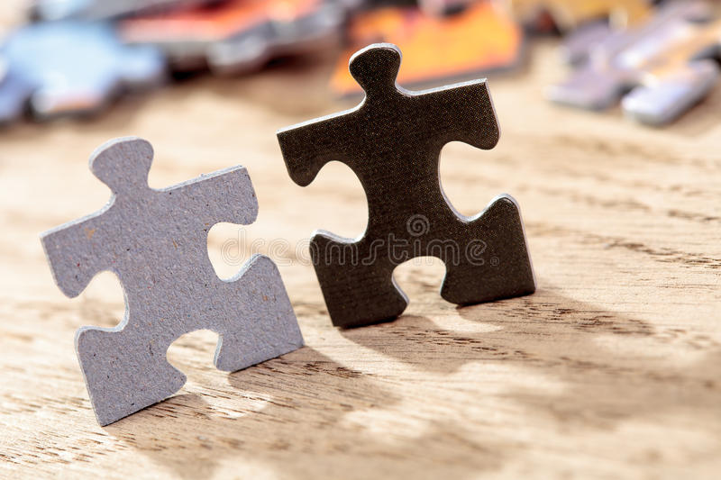 Il nero e Grey Jigsaw Puzzle Pieces sulla Tabella fotografie stock libere da diritti