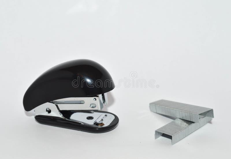 Il nero e una cucitrice meccanica e le graffette dell'argento su un fondo bianco fotografie stock libere da diritti