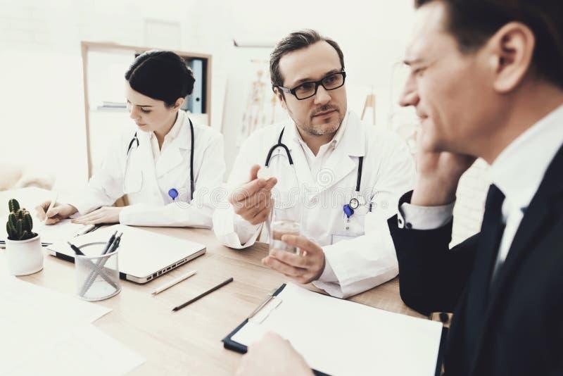 Il neurologo con esperienza diagnostica il paziente maschio con l'emicrania all'ufficio medico fotografia stock libera da diritti