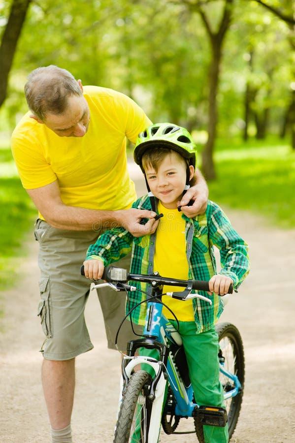 Il nonno indossa un casco della bicicletta al suo nipote immagini stock