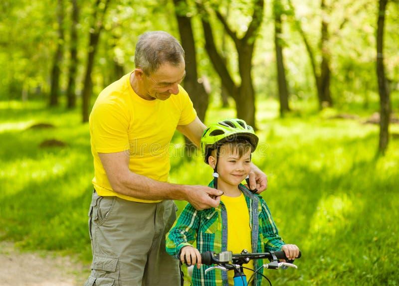 Il nonno indossa un casco della bicicletta al suo nipote immagini stock libere da diritti