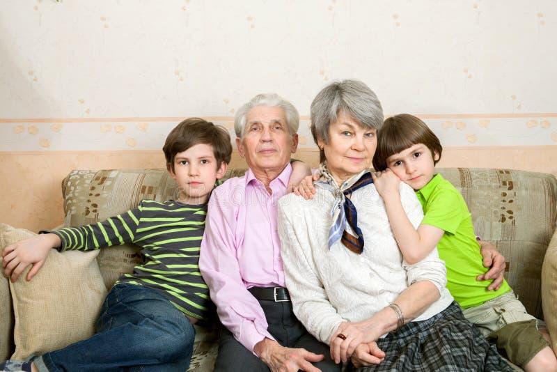 Il nonno, la nonna ed i nipoti stanno sedendo sul sofà fotografia stock libera da diritti