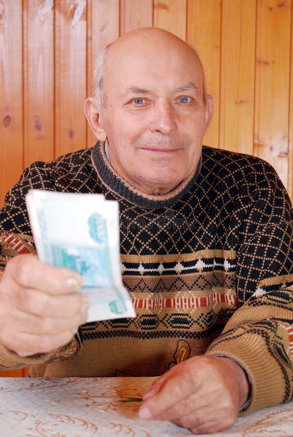 Il nonno in un maglione allunga i soldi che tiene a disposizione immagine stock