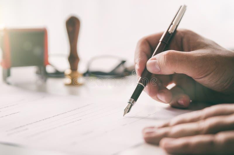 Il notaio firma il contratto legale Uomo d'affari che lavora nell'ufficio fotografie stock libere da diritti