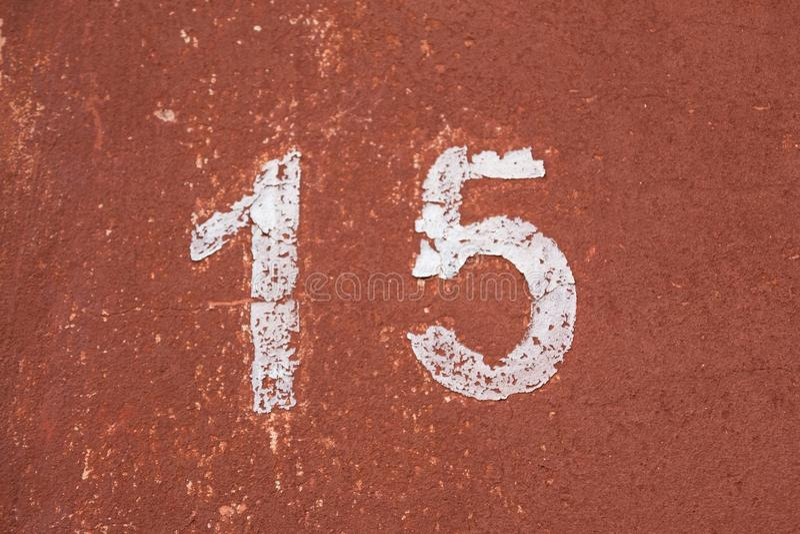 Il numero quindici nel bianco su una vecchia parete rossa fotografia stock