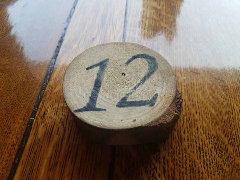 Il numero 12 su un pezzo di legno circolare su una tavola di legno incerata fotografia stock