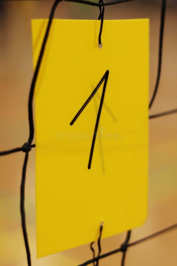 Il numero uno scritto dall'indicatore nero sulla carta di plastica gialla tiene sulla rete di pallavolo Numero usato per identifi immagine stock