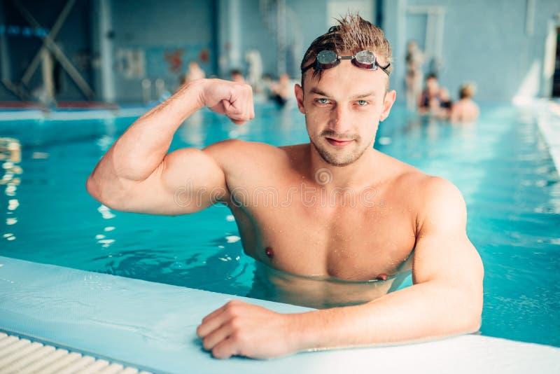 Il nuotatore atletico mostra i muscoli, sport dell'acqua fotografie stock libere da diritti