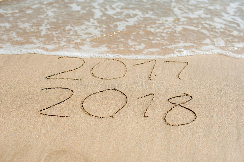 Il nuovo anno 2018 è concetto venente - le iscrizioni 2017 e 2018 su una sabbia della spiaggia, l'onda quasi stanno riguardando l fotografia stock