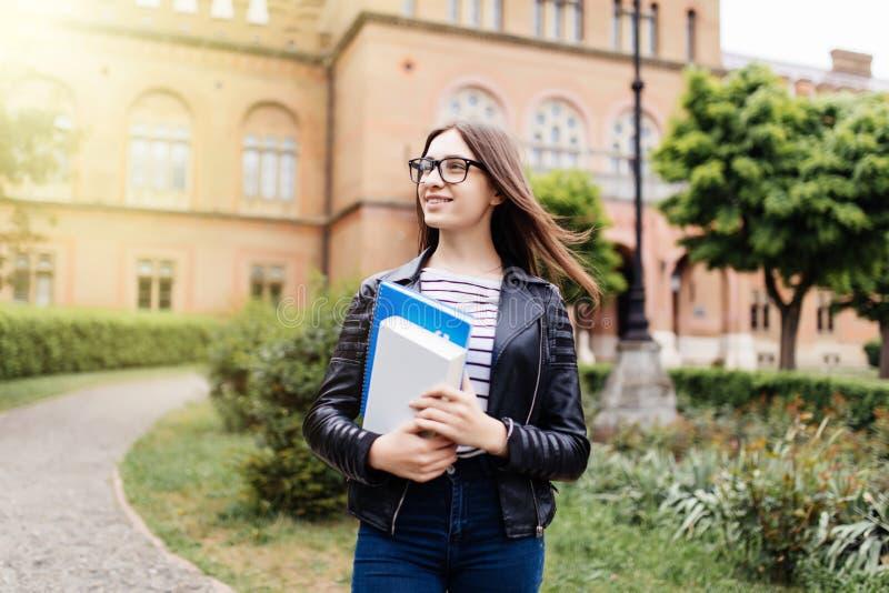 Il nuovo anno di studio comincia Studentessa che tiene i taccuini all'aperto e che sorride Uni sul fondo fotografia stock libera da diritti