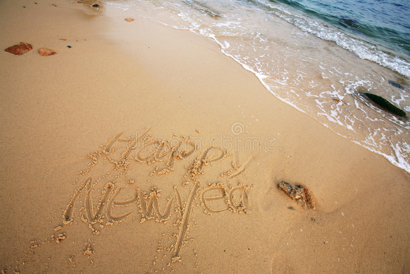 Il nuovo anno felice scrive sulla spiaggia immagini stock