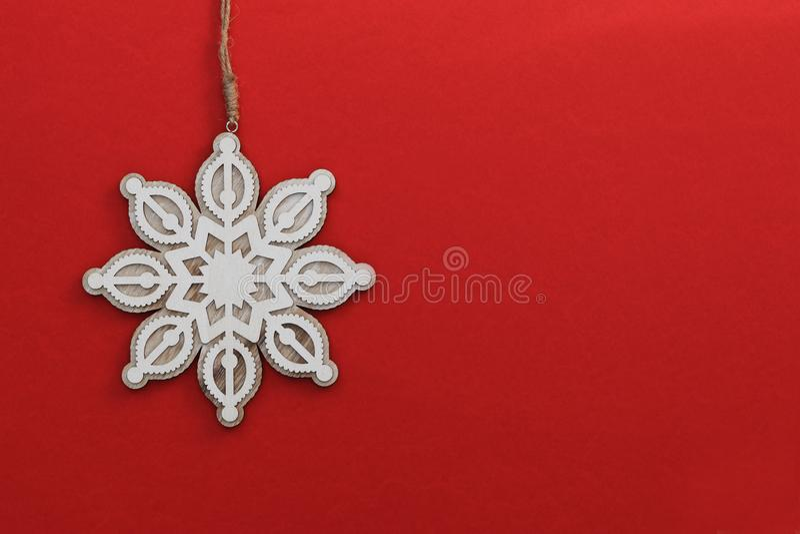 Il nuovo anno ha scolpito il fiocco di neve di legno del giocattolo con la cordicella del mestiere su fondo rosso luminoso Concet fotografia stock libera da diritti