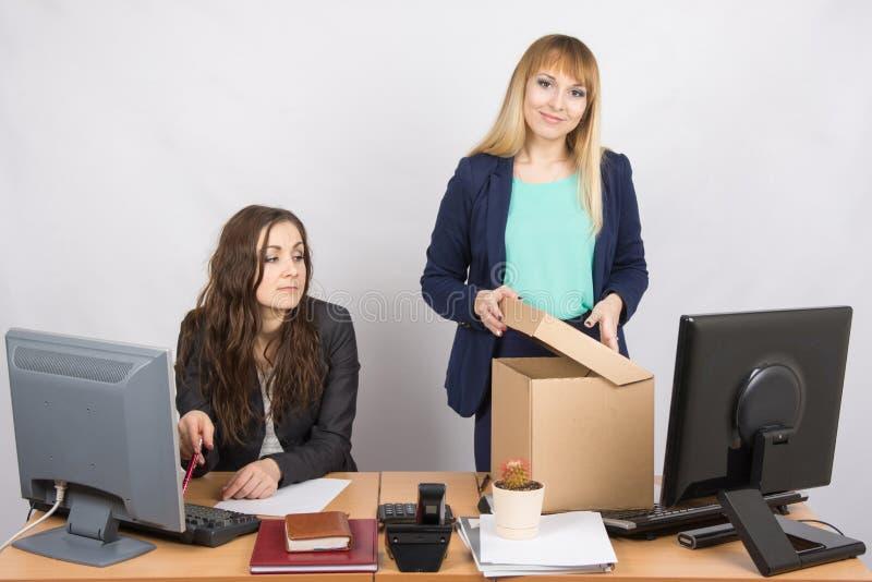 Il nuovo impiegato nell'ufficio sistema felicemente le cose, accanto ad un collega fotografie stock