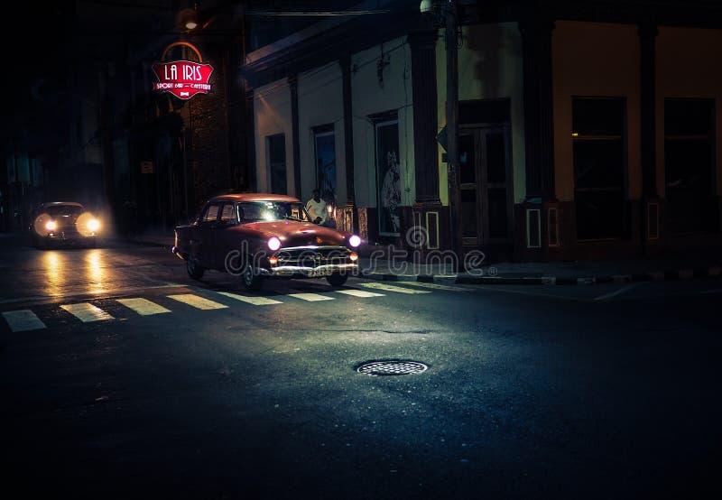 Il oldtimer rosso scuro passa le strade trasversali alla notte sotto il lampione immagine stock libera da diritti