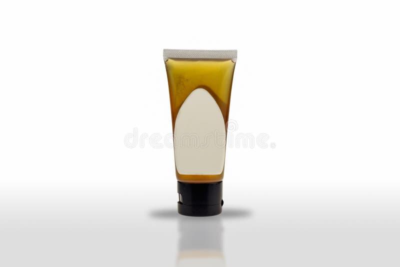 Il pacchetto di plastica del tubo che contiene il prodotto ha un'etichetta bianca isolata su fondo bianco fotografia stock