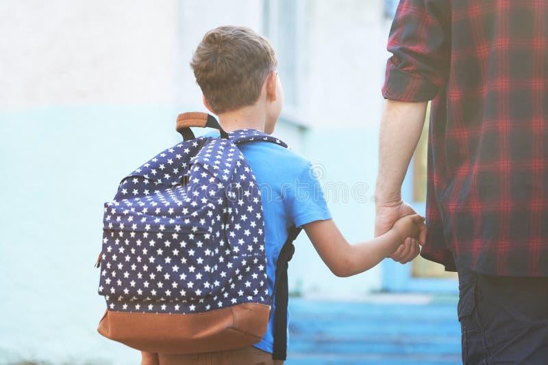 Il padre accompagna il bambino a scuola un uomo con un bambino rimosso dal retro padre che tiene la mano del figlio che va a immagine stock