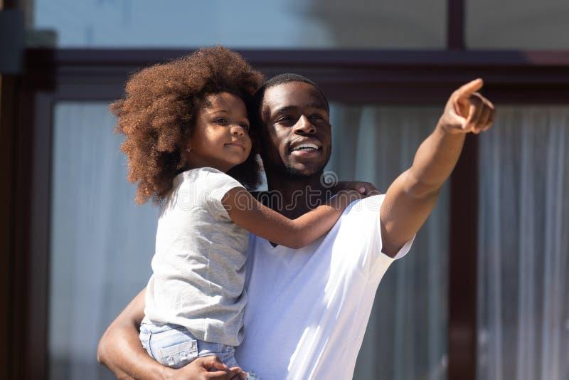 Il padre africano giudica la figlia sulle mani che mostrano qualche cosa di interessante fotografie stock