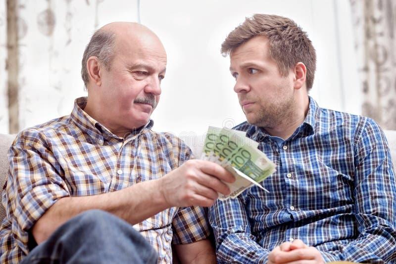 Il padre anziano presta i soldi a suo figlio adulto fotografia stock