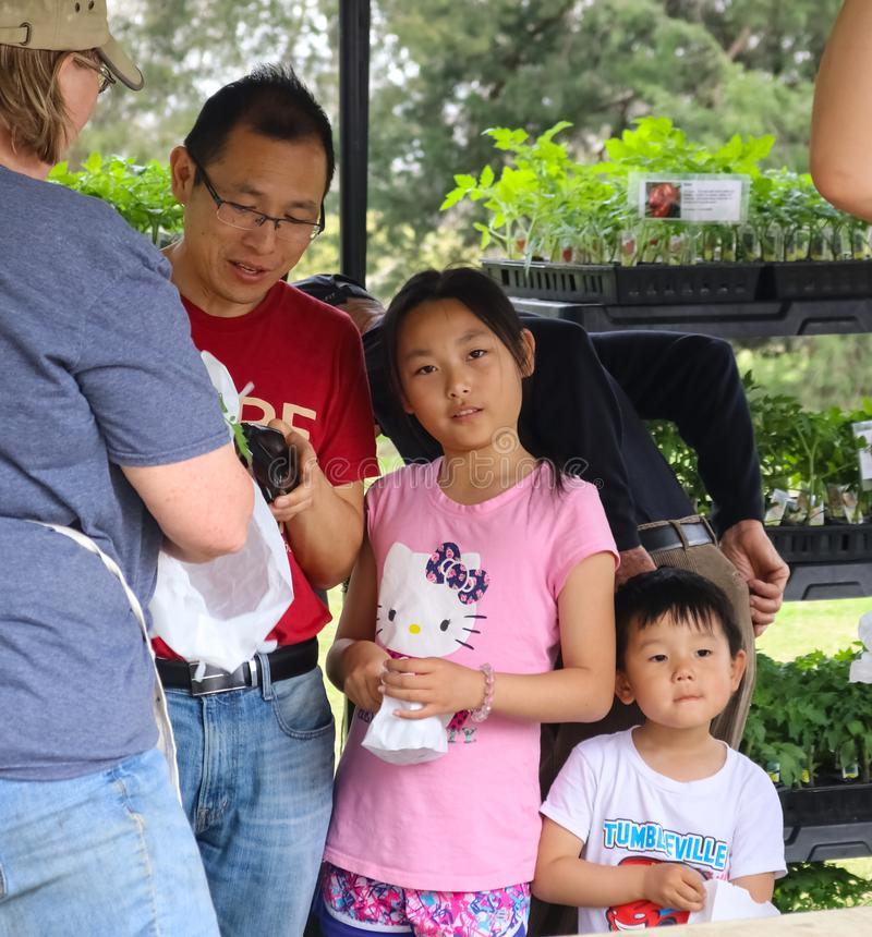 Il padre asiatico di eredità con le piante dei buys del figlio e del derivato al giardino mostra a Tulsa Oklahoma U.S.A. 4 13 201 fotografia stock libera da diritti