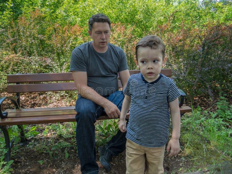 Il padre aying qualcosa a suo figlio che va via ma che ascolta fotografia stock