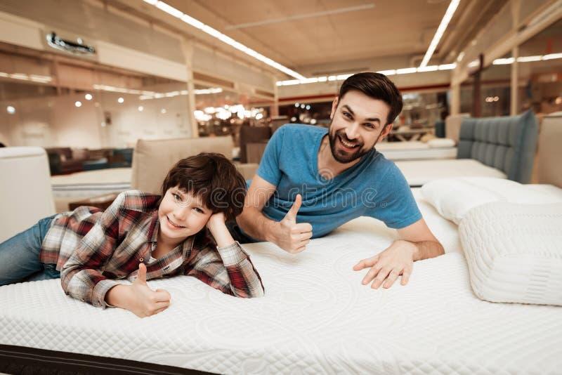 Il padre barbuto bello con il giovane figlio sta provando il materasso a morbidezza fotografia stock libera da diritti