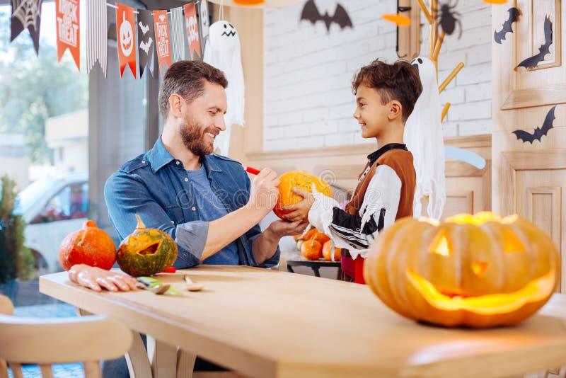 Il padre barbuto preoccupantesi che aiuta suo figlio che indossa Halloween costume la zucca della pittura fotografia stock libera da diritti