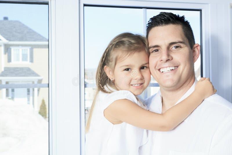 Il padre con è figlia vicino ad una finestra fotografie stock libere da diritti